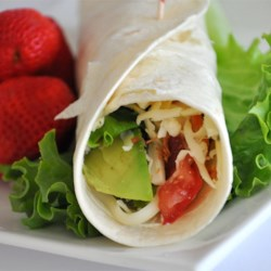 Turkey Wraps Recipe - Thin deli turkey is wrapped in a whole wheat tortilla with avocado, Swiss cheese, and crumbled bacon for an easy lunch on the go.