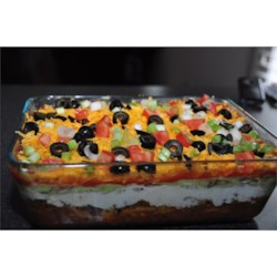 Seven Layer Dip II Recipe - My mom's Seven Layer Dip is a big hit at all small gatherings! Refried beans are layered with guacamole, seasoned sour cream, veggies and cheese. It's perfect for dipping tortilla chips! The dip traditionally takes less time to disappear into bellies than it does to prepare.