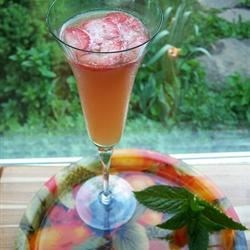 Juicy Fruit Punch with Champagne Recipe - This is a great adult punch for any time you want to celebrate. Orange, cranberry, apple and a splash of pineapple juice combine with champagne and sliced strawberries.