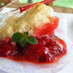 Strawberry Cobbler I Recipe - Whole strawberries are combined with a thick syrup and topped with a cream-based dough. This luscious cobbler is baked until the strawberries are bubbling away and the top is brown and beautiful.