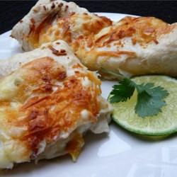 Swiss Enchiladas Recipe - Fried corn tortillas are filled with a mixture of chicken, green chilies, green chile salsa, and cream; then topped with Jack cheese, and baked to a delicious finish.