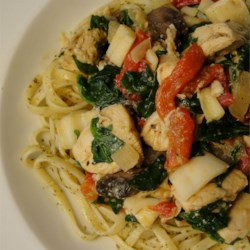 Spence's Pesto Chicken Pasta Recipe - A lovely and colorful pasta dish combines chicken with garlic, mushrooms, red peppers, artichoke hearts, spinach, and basil pesto. It's easy and quick, but looks and tastes elegant and special.