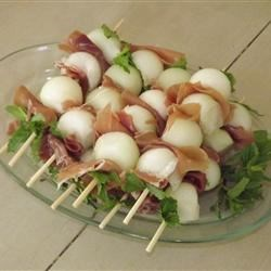 Prosciutto Wrapped Melon Balls Recipe - This is a great snack to make for any gathering. Balls of honeydew melon are wrapped in prosciutto and fresh mint to make a fancy appetizer with few ingredients.