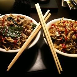 Asian Carryout Noodles Recipe - A fragrant stir-fry of onion, garlic, chicken, fresh ginger and bok choy is flavored with sesame oil, sherry, soy sauce and hoisin sauce and served over warm angel hair pasta. Sprinkle with sliced scallions and toasted sesame seeds.