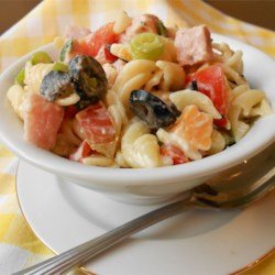 Patty's Pasta Salad Recipe - This is a hearty salad that everyone will love and fill their plates with seconds. Pepperoni, black and green olives, tomatoes, ham, and lots of mozzarella cheese. Combine all of the above with cooked pasta and a zesty Italian dressing, and you have a meal.