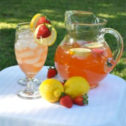 Pink Honey Lemonade Recipe - Freshly squeezed lemon juice and orange slices are combined with a sweetened strawberry mixture to create a long, cool drink for summer.