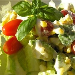 Avocado Corn Salad with Pine Nuts Recipe - Crisp romaine lettuce, kernels of tender corn, avocado slices, and cherry tomatoes are dressed with Caesar salad dressing, and sprinkled with pine nuts. Enjoy!