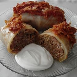 Cabbage Rolls III Recipe - These stuffed cabbage leaves are filled with ground beef, pork, rice, and onion; layered in sauerkraut; and simmered on the stovetop until done.