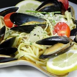 Mussels Mariniere Recipe - Fresh mussels, steamed in a fragrant broth of white wine, butter, onion, garlic, parsley, bay leaf and thyme, are arranged on linguini and served with more butter-enriched broth spooned over the top.