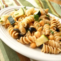 Pasta Chickpea Salad Recipe - The chickpeas make the pasta nutty and crunchy and the Parmesan cheese stirred in just before chilling adds a wonderful creaminess. There are also peas, oil-cured olives, green onions and fresh herbs. Chill overnight. Serves six.