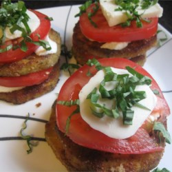 Eggplant Slices, Tomatoes, and Mozzarella Recipe - Fried eggplant slices, topped with sliced tomatoes and mozzarella, are baked until bubbling and drizzled with a garlic, basil, and anchovy-infused olive oil. This dish can be served warm or cold.