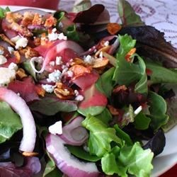 Green Salad with Cranberry Vinaigrette Recipe - Mixed greens, toasted almonds, red onion, and crumbled blue cheese are tossed in a quick, tangy cranberry dressing for an impressive and easy salad!