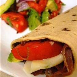 Hummus and Prosciutto Wrap Recipe - Crisp prosciutto, sliced avocado, mozzarella cheese, and tomato are rolled into a tortilla spread with hummus for a delicious quick lunch.