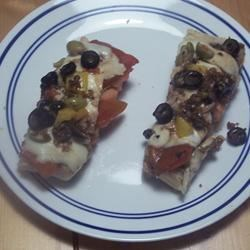Papa Felico's Garlic Sausage Bread Recipe - Italian bread is topped with sausage, tomato, mozzarella cheese, red bell pepper, and a homemade balsamic vinaigrette to make this delicious treat.