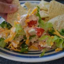 Layered Taco Dip Recipe - Taco dip layered with green onions, black olives, tomatoes, lettuce and cheese.  Serve with tortilla chips.
