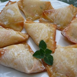 No Fry Crab Rangoon Recipe - A savory mix of cream cheese and imitation crab meat  fills these baked appetizers.