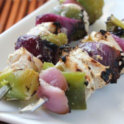 Marinated Greek Chicken Kabobs Recipe - Chicken pieces are marinated in a blend of yogurt , lemon juice, and feta, then grilled on skewers with onions and green peppers.