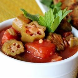 Okra with Tomatoes Recipe - Canned tomatoes and frozen okra are simmered with green bell pepper, onion, and garlic for a tasty side dish.
