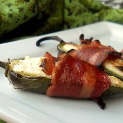 Stuffed Jalapeno Firecrackers Recipe - Beware! These yummy little appetizers are spicy times three. With jalapenos, spicy bacon, and a generous sprinkle of Cajun seasoning, you might want to have a cool beverage nearby.