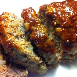 Easy Meatloaf Recipe - No-fail meatloaf calls for ground beef, onions, egg, milk, and bread. It is topped with a mix of brown sugar, mustard, and ketchup before baking.