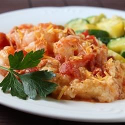 Ginger's Shrimp and Grits Recipe - Tender shrimp are cooked in a flavorful tomato sauce with green chiles, then layered with spicy, cheesy grits and baked for a Southern-style classic.