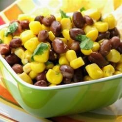 Corn and Black Bean Salad Recipe - A simple cumin dressing is tossed with a salad bowl full of kernel corn and black beans. It's sensational as is but we think it would be super rolled in a warm tortilla with a dollop of sour cream.