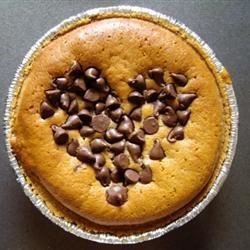Patricia's Peanut Butter Pie Recipe - Peanut butter chips are sprinkled over the bottom of the graham cracker crust. Then a sinfully delicious concoction of peanut butter, honey,  milk, and egg is spooned into that. This dreamy pie is then finished with a generous sprinkling of chopped peanuts.