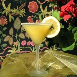 Texatini Recipe - Served in a Texas-sized martini glass, this margarita is made with sweet and sour mix and a splash of orange juice, and is garnished with a jalapeno-stuffed green olive.
