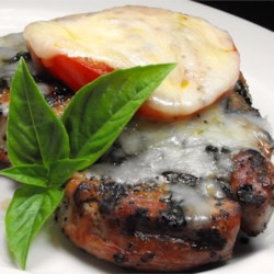 Amazing 'Pizza' Pork Chops Recipe - Topping your pork chops with tomato, basil, oregano, garlic, and mozzarella cheese will give them a pizza-like flavor.
