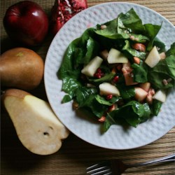 Pear and Pomegranate Salad Recipe - This colorful salad is a fall and winter favorite. It's garnished with pomegranate arils and dressed with a warm pomegranate vinaigrette.