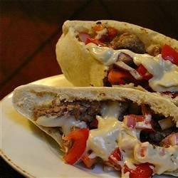Lebanese Donair Recipe - A dish that's popular in throughout the Middle East combines thinly sliced roast beef with a fragrant, spicy sauce starring cinnamon, allspice, cardamom. To serve, the meat is layered in pita rounds and topped with a fresh parsley mixture, chopped tomatoes, and savory tahini sauce.