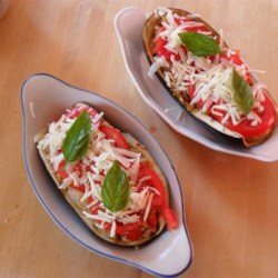 Aunt Eileen's Stuffed Eggplant Recipe - Eggplant halves are stuffed with a zesty filling, and topped with tomato slices and Gruyere cheese.