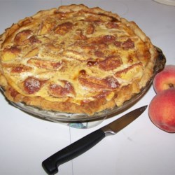 Peach Custard Pie III Recipe - Peach halves are arranged in a pie shell, and sprinkled with brown sugar and flour. A mixture of evaporated milk and egg is poured over the peaches, and before the pie is slipped into the oven, it 's dusted with sugar and spices.