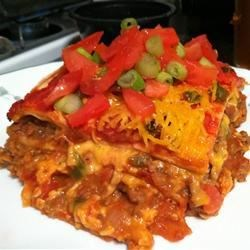 Mexican Lasagna II Recipe - Seasoned ground beef and refried beans layered with cheese and tortillas and baked until hot and bubbly.