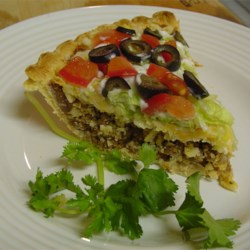 Taco Pies Recipe - Prepared pie crusts are baked briefly and packed with refried beans, browned ground beef, chopped onions, tortilla chips, and cheddar cheese. These are returned to the oven to finish baking.