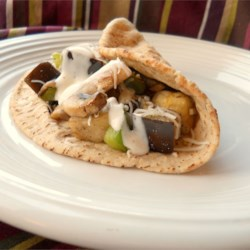 Easy Eggplant Pita Recipe - A splash of olive oil in the pan begins the process. Then the veggies are tumbled in  - chopped eggplant, mushrooms, onion, and bell pepper. A shake of garlic powder, and when everything is cooked and yummy, it 's plopped into a pita pocket. Top with Mozzarella cheese, and serve.