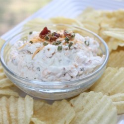 Baked Potato Dip II  Recipe - Classic toppings including sour cream, Cheddar cheese, green onions, and bacon are mixed up in this family-friendly appetizer. Serve this dip with thick cut potato chips for even more baked potato flavor.