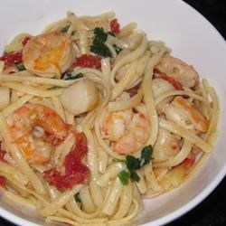 Linguine with Seafood and Sundried Tomatoes Recipe - Tender whole scallops and shrimp get a quick saute in hot, garlicky olive oil and butter before taking a brief clam juice simmer. Toss with hot pasta, bright strips of sun dried tomatoes and tangy bits of lemon zest for a refreshing entree or appetizer.
