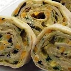 Spicy Tortilla Roll-Ups Recipe - This vegetarian special gets its bite from canned green chiles and hot pepper sauce; cream cheese cools things down.