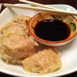Pork Dumplings Recipe - Delectable dim sum is at your fingertips with this amazingly easy recipe. A tasty mixture of ground pork, fresh ginger, garlic, green onion, soy sauce, sesame oil, egg and Chinese cabbage is rolled into wonton skins. Steam and serve to party guests.