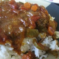 Slow Cooker Sloppy Swiss Steak Recipe - Floured pieces of beef round steak slowly cook to melting tenderness in a sloppy-joe-like sauce with green peppers, onions, and carrots to lend a hint of sweetness.