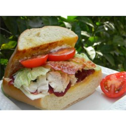 Turkey Sandwiches with Cranberry Sauce Recipe - Layer French bread wedges with sliced turkey, bacon, Provolone cheese, tomatoes, and jellied cranberry sauce to make a hearty broiled sandwich with the taste of Thanksgiving.