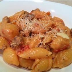 Cheesy Sausage Pasta Recipe - Seashell pasta is bathed in a luxurious sausage and tomato cheese sauce to create the ultimate macaroni dish.