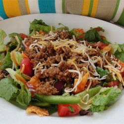 Taco Salad III Recipe - Seasoned ground beef, pinto and kidney beans, lettuce, tomatoes, Cheddar cheese, and avocado round out this hearty main dish salad. It's topped with crushed corn chips and Catalina dressing.