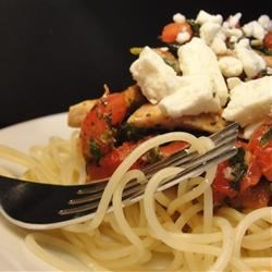 California Chicken Spaghetti Recipe - Angel hair pasta is tossed with chicken and roma tomatoes in this simple but flavorful dish. The spicy blackened meat seasoning combines well with the crumbled feta cheese.  Easy, but great for a company dinner!
