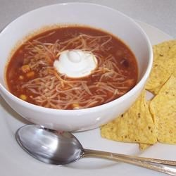 Becca's Taco Soup Recipe - Taco ingredients such as browned ground beef, onion, corn, kidney beans and a package of seasoning mix are combined in this soup which may be garnished with grated cheese.  Serve with tortilla chips.