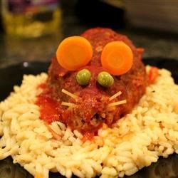 Halloween Bloody Baked Rats Recipe and Video - This is a fun, inexpensive, creepy Halloween entree that will gross out and impress your dinner guests. It is  mini meatloaves baked in tomato sauce that are shaped like rats with cheese in the middle. When you cut  it open, gooey cheese will come oozing out. Garnished with a spaghetti noodle tail and carrot ears, these pests are sure to be a devilishly delectable dinner.