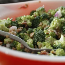 Fresh Broccoli Salad Recipe and Video - Broccoli, crumbled bacon, raisins and nuts, with a smattering of red onion tossed in a mayonnaise based dressing gives this salad bite, crunch, and sweetness..