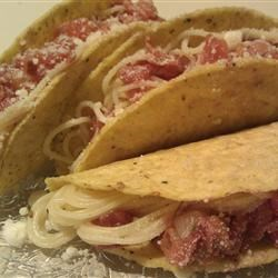 Spaghetti Tacos Recipe - Inspired by an episode of a popular kids' comedy TV show, these fun spaghetti tacos are fast and simple to make. Just load a crispy taco shell with pasta and premade sauce, sprinkle with some Parmesan, and eat!
