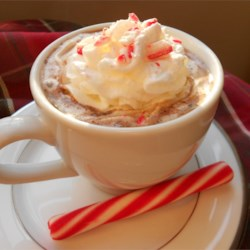 Candy Cane Cocoa Recipe - Milk is heated with semisweet chocolate and crushed candy canes. Then each mug is garnished with whipped cream and a small candy cane.